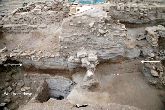 Forteresse hellénistique, tranchée sud. À gauche, le puits, à droite la stratigraphie de la rue. Les flèches indiquent le niveau de la première rue hellénistique. Vue vers le sud © MAFKF