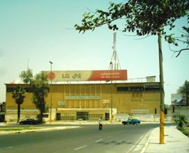 الشكل 2 : ( يمينا) الواجهة الأمامية على الشارع، لقطة من أحد تقارير الطلبة في جامعة بغداد، 2005. الواجهة الرئيسية المنحنية تؤسس للمشروع الحضري لهذا المجمع.