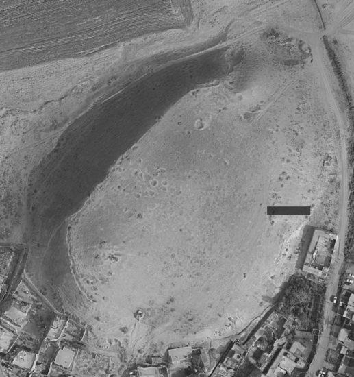 Figure 2 : le site d'Amyan, composé d'un tell et d'une ville basse partiellement recouverte par un village moderne ; la tranchée du secteur A est en noir (d'après https://www.bing.com/maps)